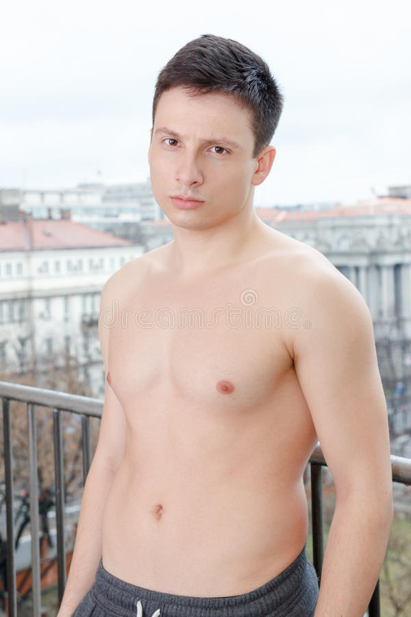 Attractive shirtless young thoughtful man posing outdoors. Guy with naked torso standing on balcony leaning on fence wearing only sweatpants stock image