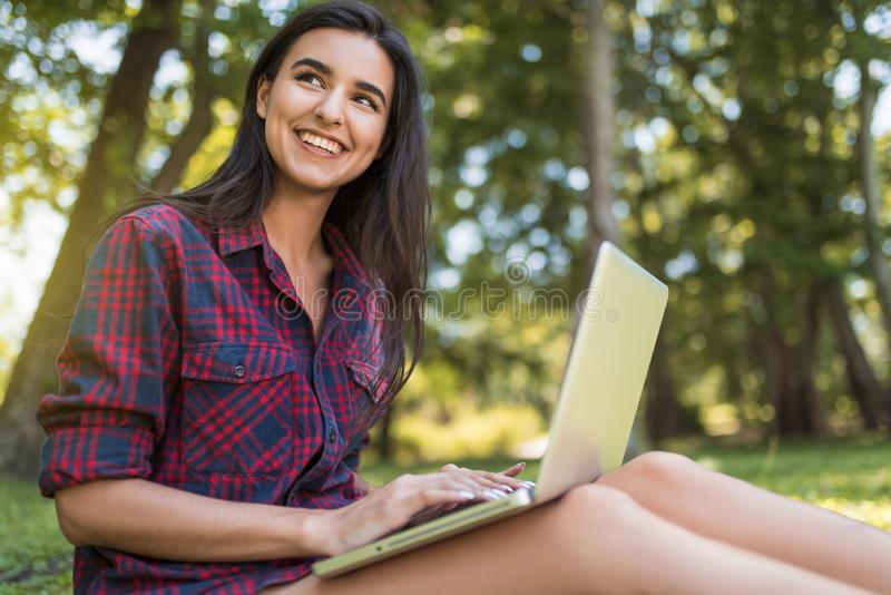 Attractive shot of young Caucasian happy female wearing plaid shirt, sitting on grass in front of laptop pc, working on her laptop stock photo