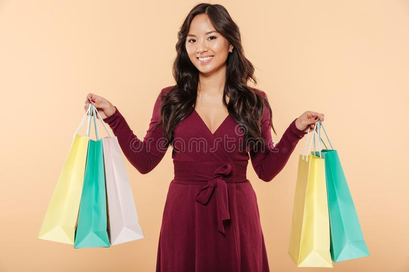 Attractive sian woman in elegant maroon dress shopping and showing packs with purchases over beige background. Attractive sian woman in elegant maroon dress stock photos