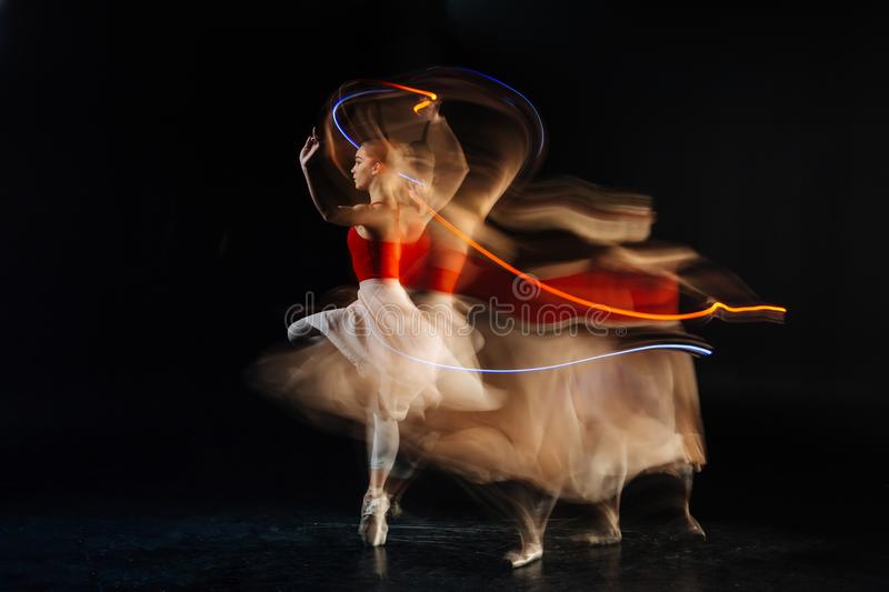 Attractive skillful woman showing her performance. Dance show. Attractive skillful young woman dancing and showing her performance while standing against black stock photos
