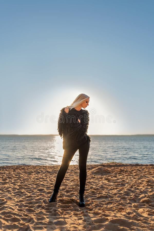 Attractive slender person girl blonde stands posing on the shore of the water in black clothes with a background of the rising sun. Attractive beautiful young stock photography