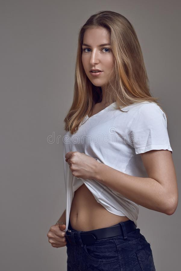 Attractive slender sexy young blond woman in jeans and a white T-shirt stock photography