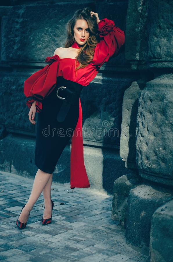 Attractive slender woman in a sleek elegant blouse and a black skirt walking through the city. A lot of photos. stock photo