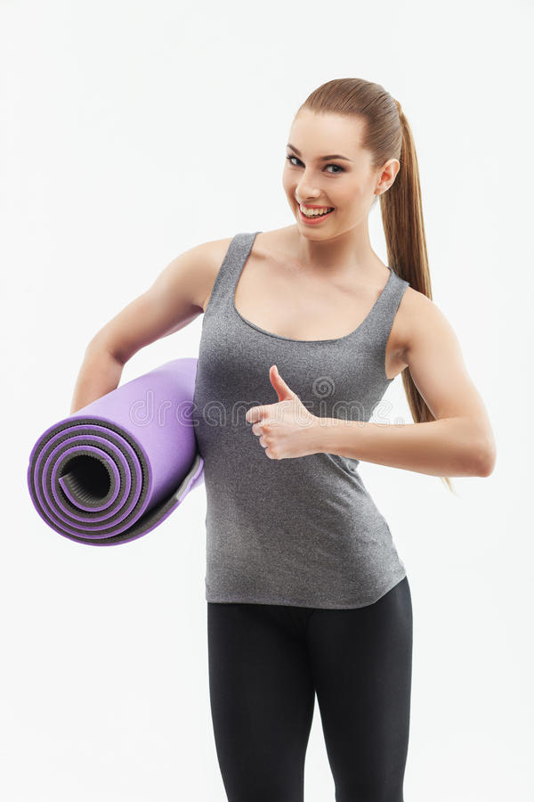 Attractive slim girl with an exercise carpet stock photo