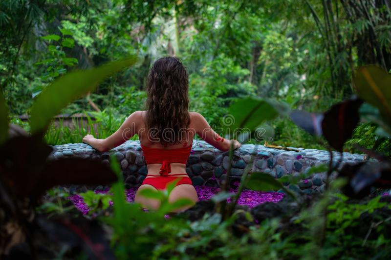 Attractive slim girl is standing back in the jungle. Brunette model in in the pool of flowers. Spa, relaxing. model royalty free stock photos