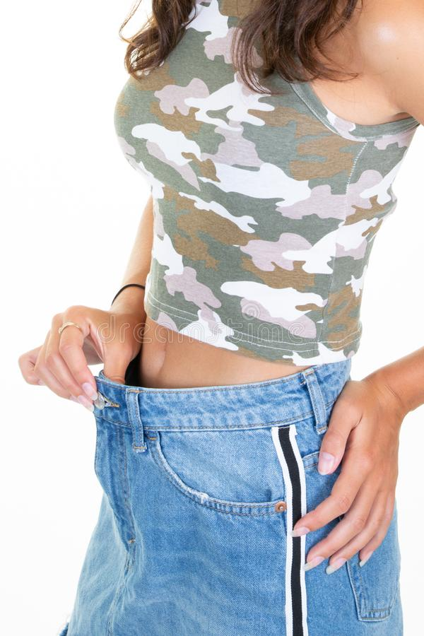 Attractive slim woman in blue jeans skirt showing successful weight loss results. An Attractive slim woman in blue jeans skirt showing successful weight loss stock image