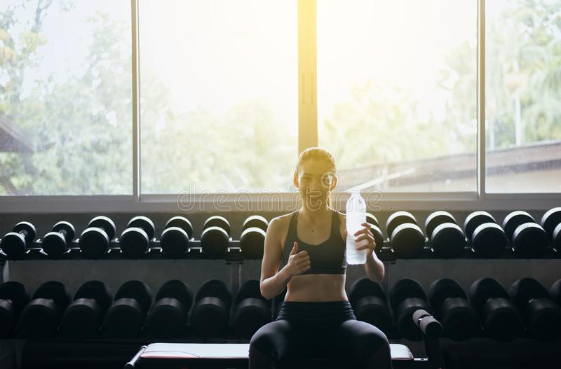 Attractive slim woman showing thumb up and drinking water in gym,Asian female break and relax after workout royalty free stock images