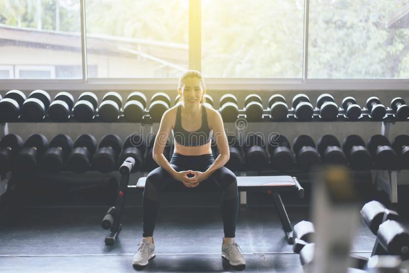 Attractive slim woman sitting at gym in the morning,Asian female break and relax after workout stock photos