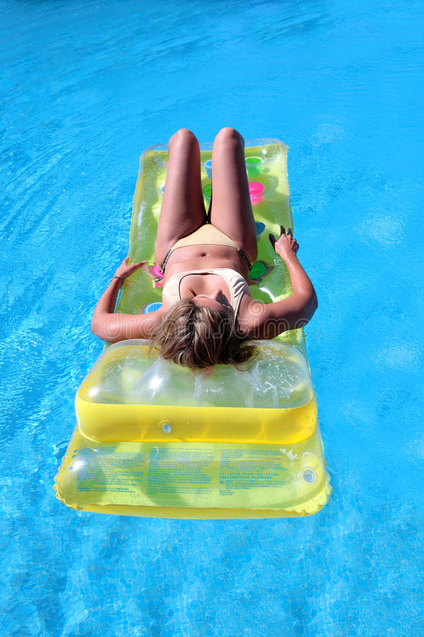 Attractive, slim young lady lying on inflatable sunbed on swimming pool stock photography