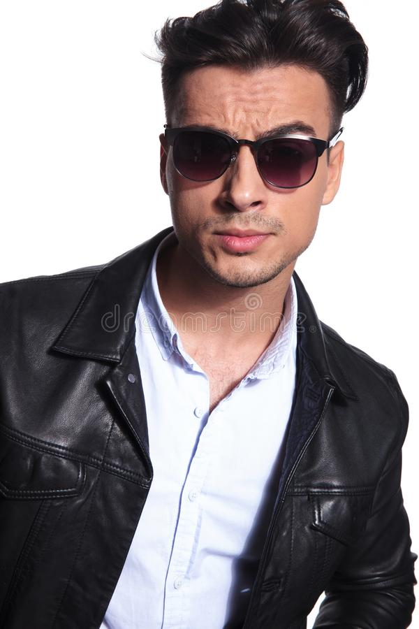 Attractive smart casual man in leather jacket wearing red sunglasses stock image