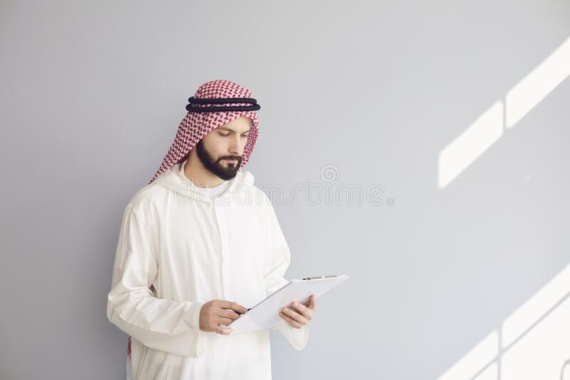 Attractive smiling arab man writes in clipboard on gray background stock photo