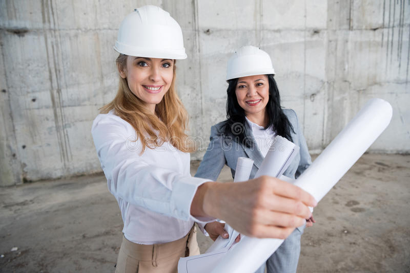 Attractive smiling architects holding blueprint while working at construction site royalty free stock photos