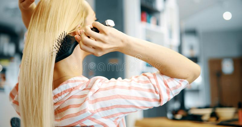 Attractive smiling woman brushing her hair stock image