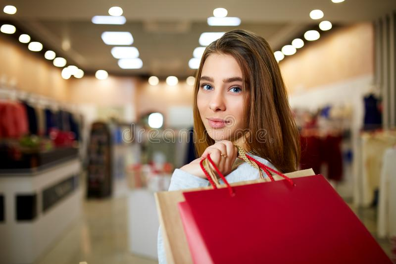 Attractive smiling blonde on shopping in mall. Pretty caucasian girl holding colorfull shopping bags with copyspace in stock photos