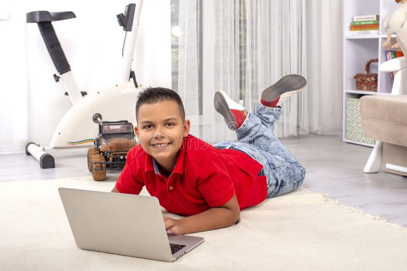 A schoolboy  is lying at a floor with a laptop in the room.  He does his homework or emotionally plays computer games or stock photos