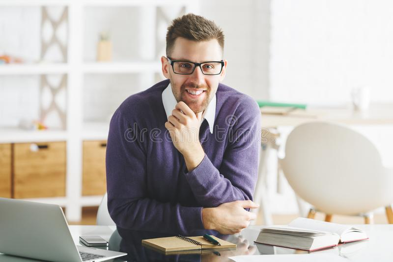 Attractive smiling businessman working on project. Portrait of attractive smiling businessman working on project at modern office desk with items. Job royalty free stock photos