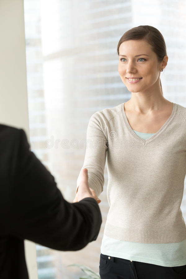 Attractive smiling businesswoman shaking male hand, nice to meet. You, business etiquette gesture at first meeting, greeting handshake at job interview, making stock photography