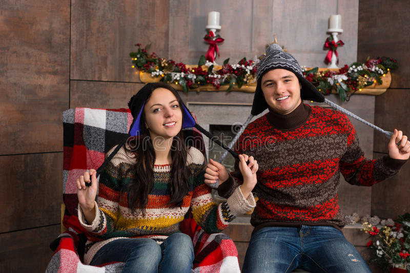 Attractive smiling couple in funny knitted Nordic hats sitting i. N a rocking chair near decorated fireplace in the living room stock image