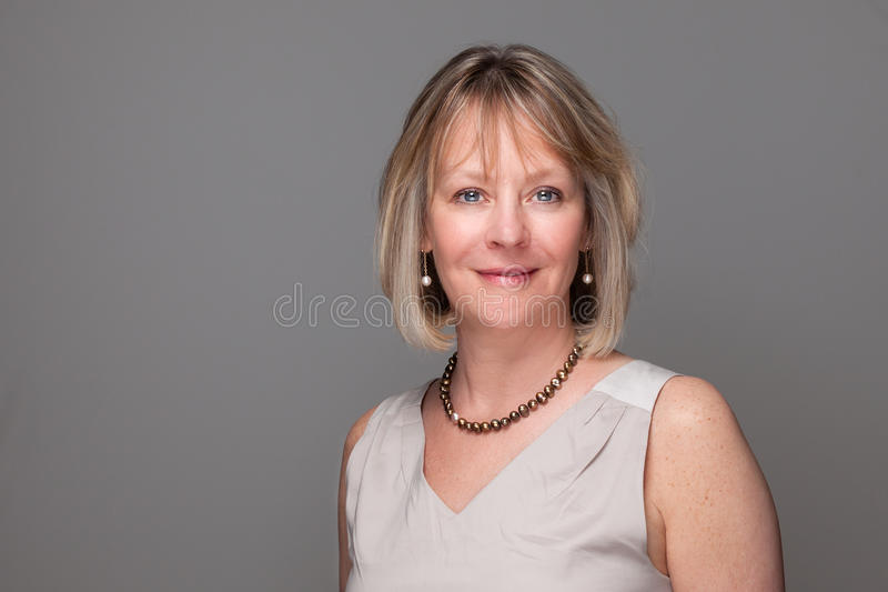 Attractive Smiling Elegant Woman on Grey royalty free stock photography