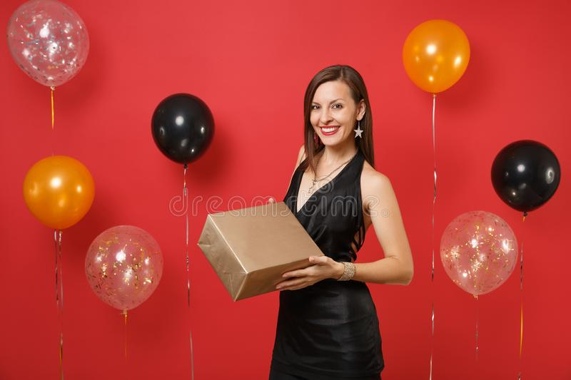 Attractive smiling girl in black dress celebrating, holding golden box with gift, present on bright red background air stock images