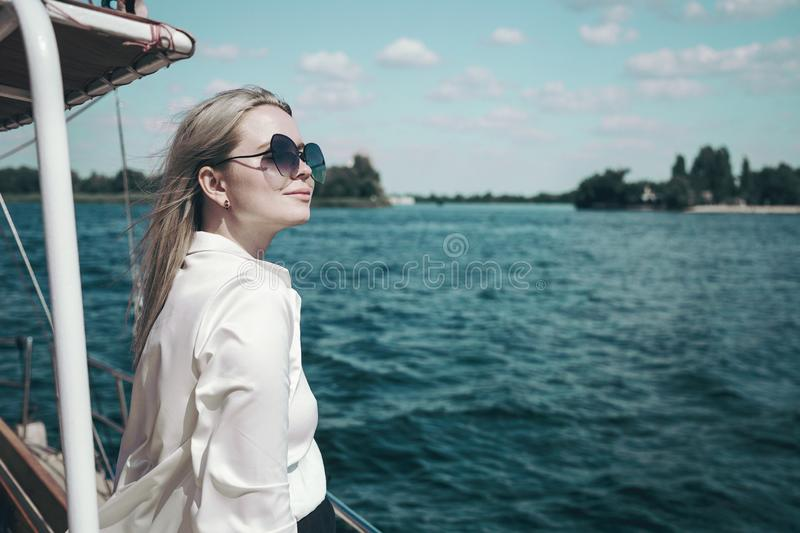 Attractive smiling girl in a white shirt and sunglasses on a yacht. The concept of yachting or cruise on the sea or stock images
