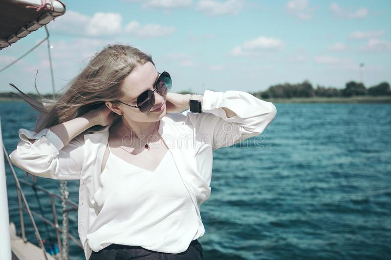 Attractive smiling girl in a white shirt and sunglasses on a yacht. The concept of yachting or cruise on the sea or royalty free stock photo