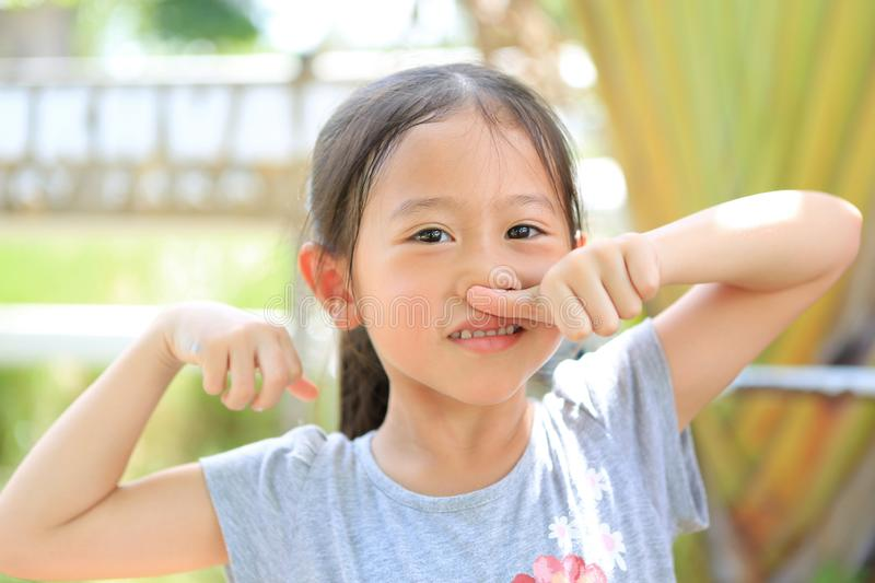 Attractive smiling little child girl touching nose with thumb with expression happy and relax outdoor. Portrait Asian kid in royalty free stock photography