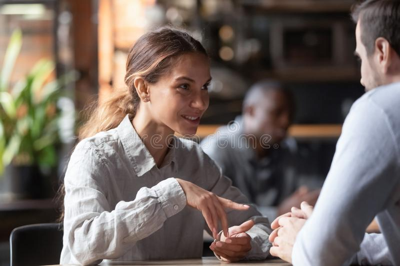 Attractive smiling mixed race woman chatting with man in coffeehouse stock photos