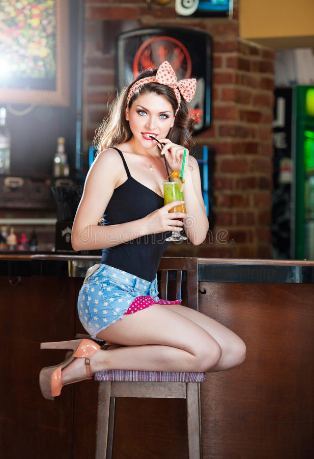 Attractive smiling pinup woman in denim shorts sitting on bar stool and drinking lemonade stock image