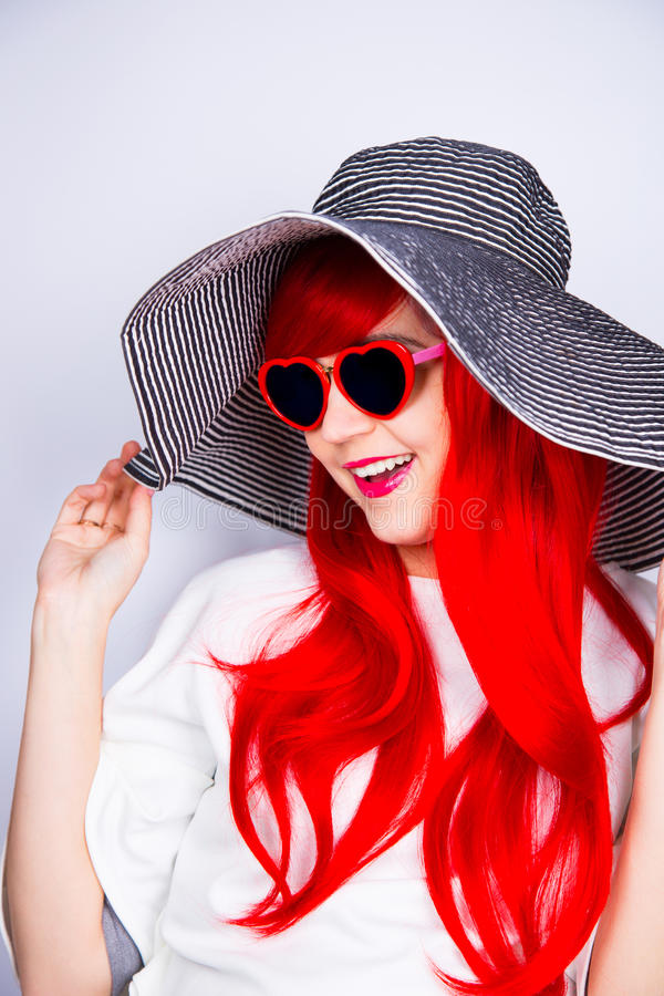 Attractive smiling red-haired young woman in sunglasses and hat stock images
