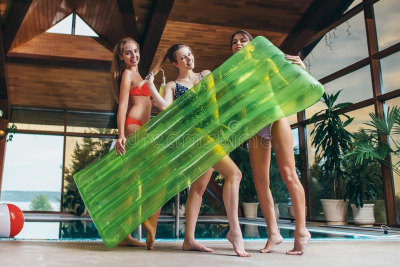 Attractive smiling slim female friends wearing swimsuits holding inflatable lounge posing in spa and wellness center.  stock images