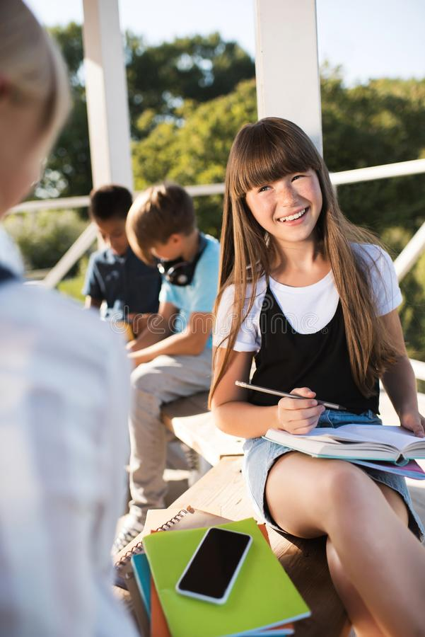 Smiling teenager studying with books royalty free stock photography