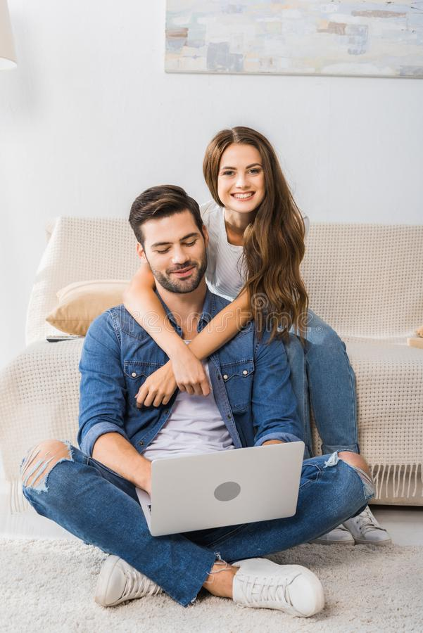 attractive smiling woman embracing boyfriend while he using laptop sitting on floor stock images