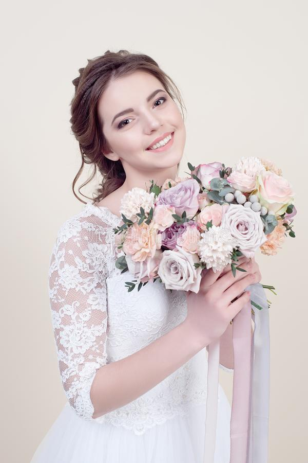 Attractive smiling woman holding a bouquet of flowers wearing in luxurious wedding dress isolated on background royalty free stock images