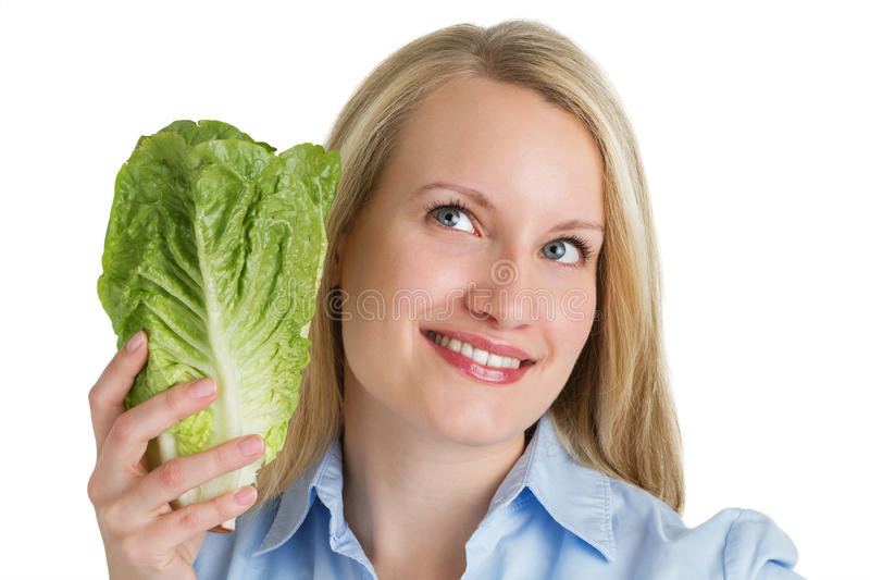 Attractive smiling woman holding fresh lettuce royalty free stock photography