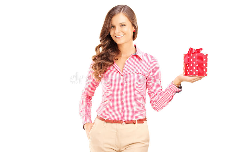 Attractive smiling woman holding a gift box and posing stock photo