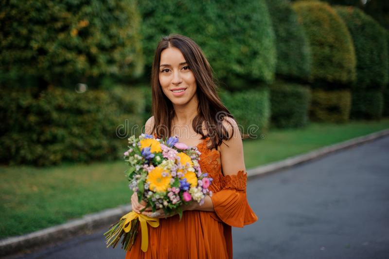 Attractive smiling woman in orange dress holding a bouquet of flowers stock images