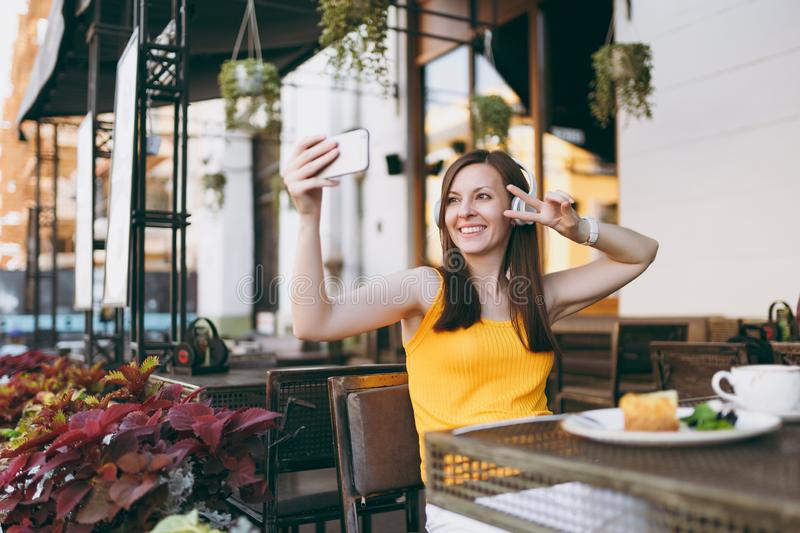 Attractive smiling woman in outdoors street coffee shop cafe sitting at table, listen music in headphones, doing selfie stock photo