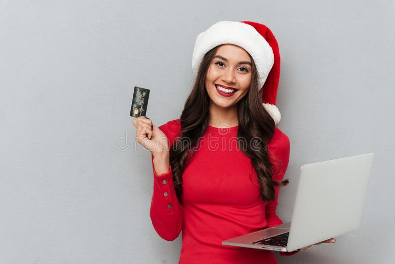 Attractive smiling woman in Santa`s hat holding credit card and. Laptop computer, looking at camera, on gray background stock photos