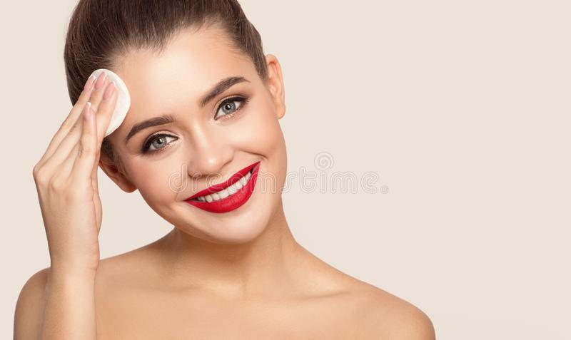 Attractive smiling woman using cotton pad. stock images