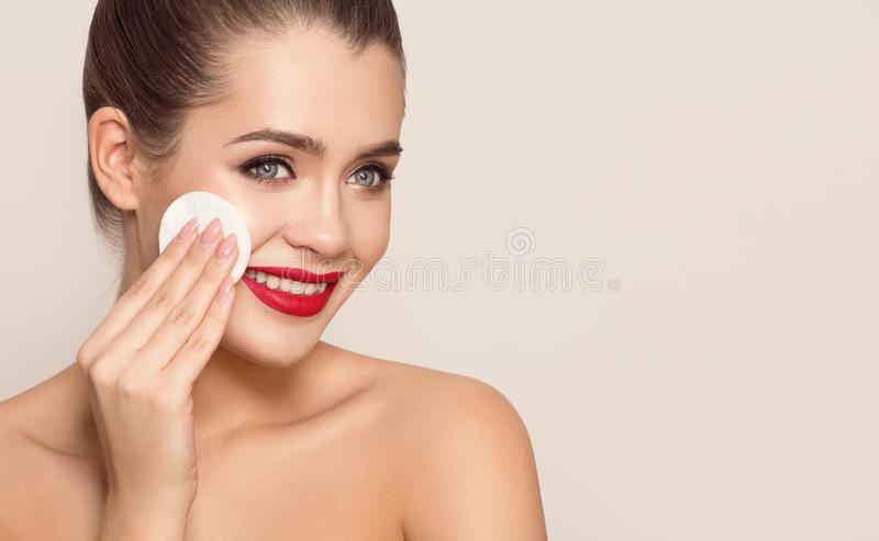 Attractive smiling woman using cotton pad. royalty free stock images