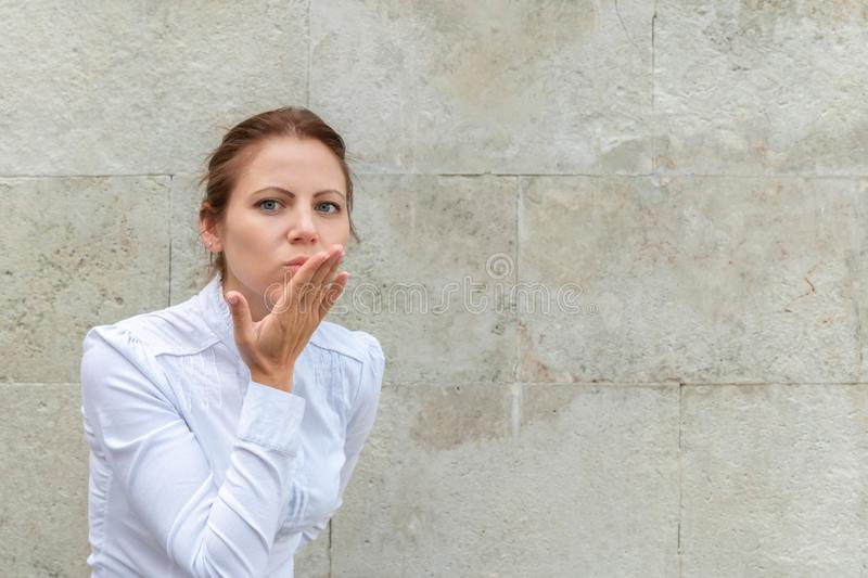 Smiling woman blowing air kiss sign gesture on urban wall background with copy space royalty free stock photos