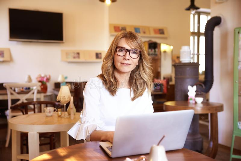 Attractive smiling woman working on laptop in small cafe stock image