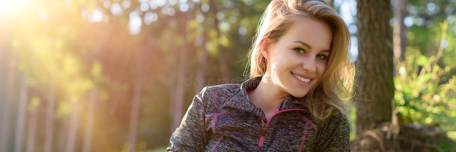 Attractive smiling young blond woman, wearing sportswear, relaxing after workout in a forest. royalty free stock photos