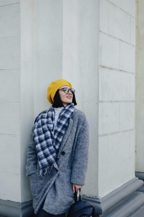 Attractive smiling young girl in glasses in coat and yellow Beret on a simple light background stock images