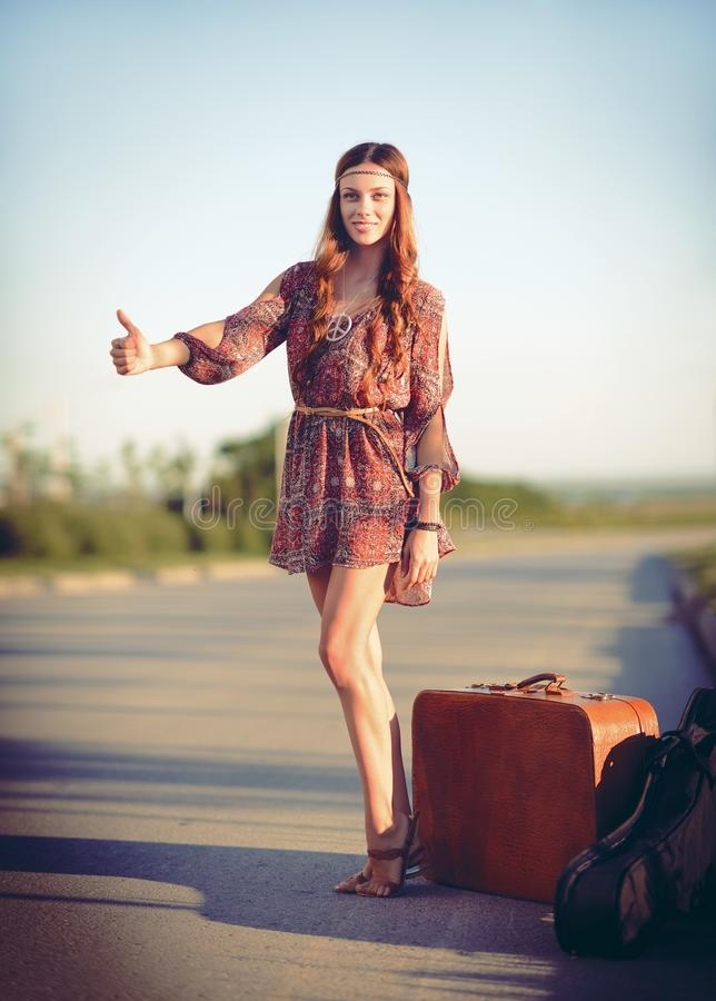 Attractive smiling young hippie woman hitchhiking on a road at sunset time. Attractive smiling young hippie woman hitchhiking on the road at sunset time royalty free stock images