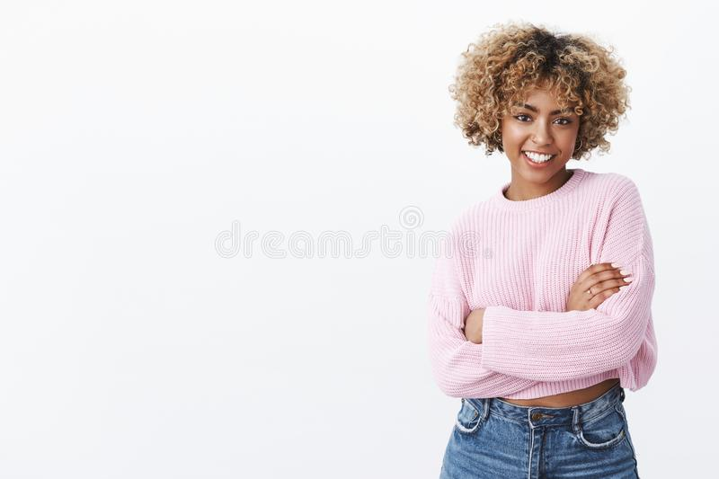 Attractive sociable and charismatic african-american female 20s with curly blond hair in warm winter sweater holding. Herself with hands crossed over body and stock image