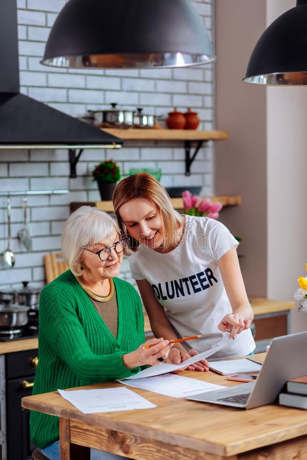 Attractive social worker assisting granny in figuring out with papers. Social help for old people. Attractive nice social worker kindly assisting silver-haired royalty free stock images