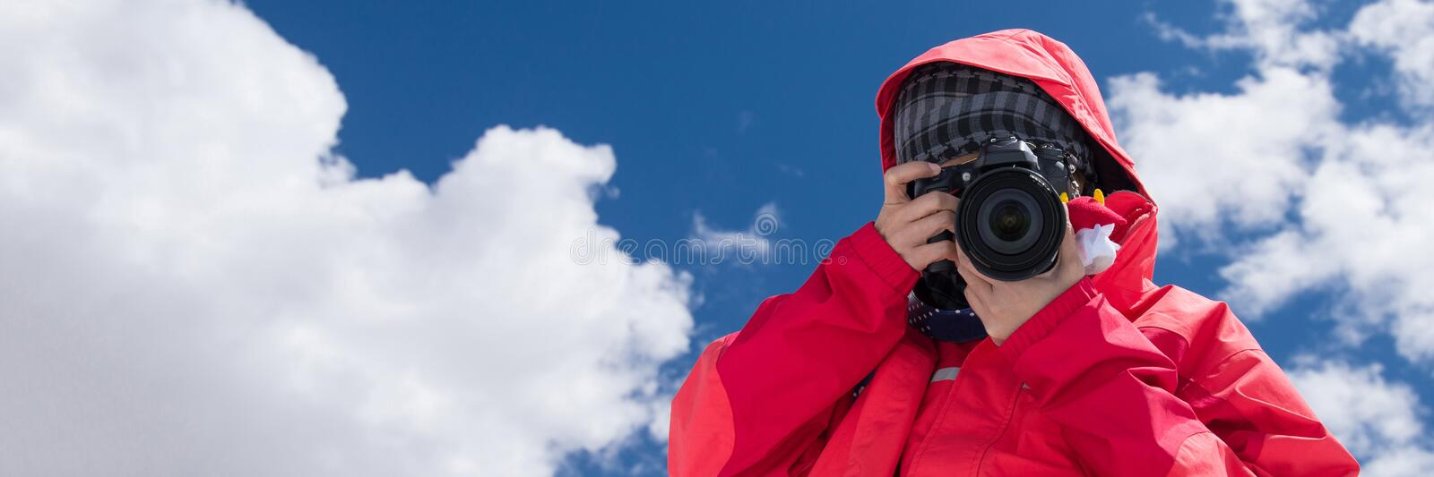 Attractive solo women traveller talking pictures outdoors with blue sky background royalty free stock photography