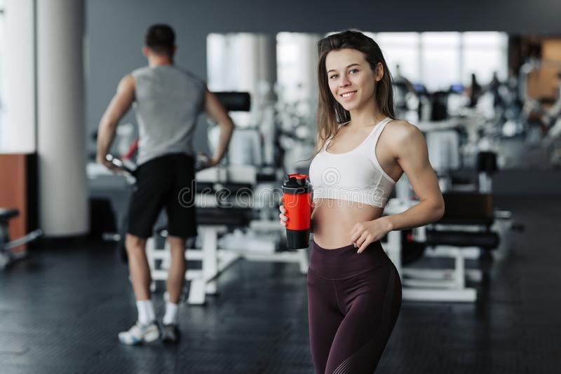 Attractive sport girl smiling and drinking water while standing at the gym with the boy training on background stock image